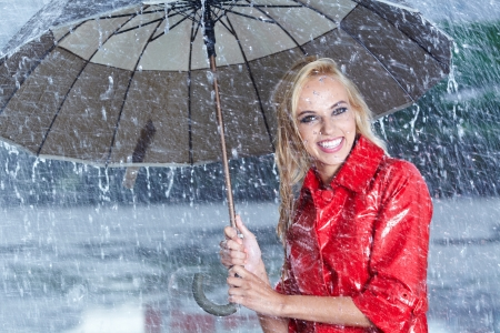 Woman in raincoat smiling as she holds umbrella  photo