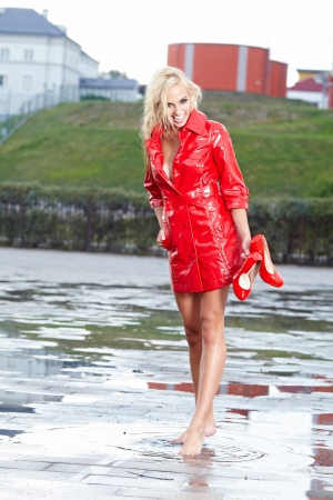 Young sexy girl walking along wet street after rain  photo