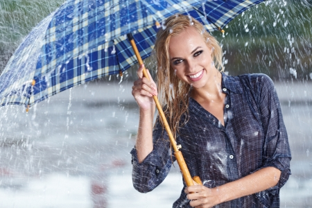 Beautiful sexy woman with blue  umbrella on rainy day  photo