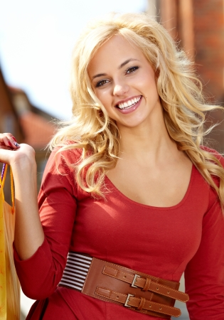 outsides: blond woman with many small shopping bags