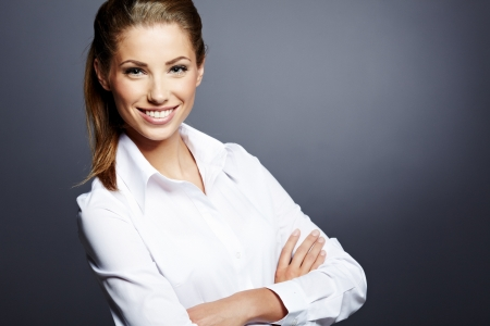 Portrait of a beautiful young business woman standing against grey background  Stock Photo