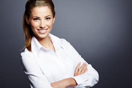 confianza: Retrato de una mujer de negocios hermosa joven de pie contra el fondo gris