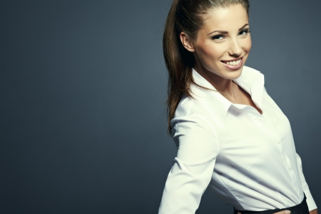 Portrait of a beautiful young business woman standing against grey background  photo