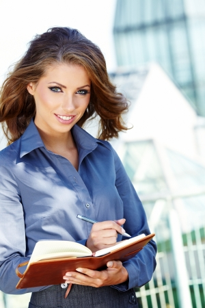 agents: Beautiful young businesswoman among the constructions of the modern building
