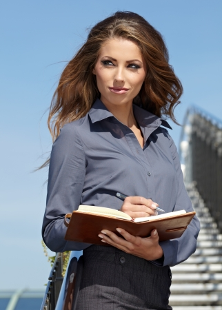 Beautiful young businesswoman among the constructions of the modern building