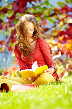 Portrait of beautiful young brunette girl reading a book in the park at fall   photo
