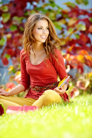Student smiling against a autumn leaves  background photo
