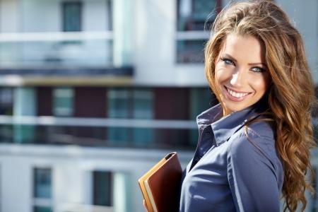 Businesswoman standing outside a modern house  Zdjęcie Seryjne