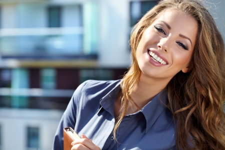 Businesswoman standing outside a modern house Stock Photo - 15030557