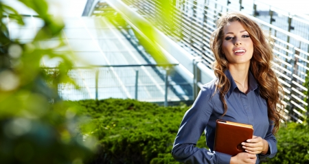 Businesswoman standing outside a modern house Stock Photo - 15030604
