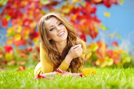 Portrait of a gorgeous brunette woman reading a book in the autumn  park   photo