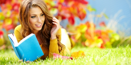 Portrait of a gorgeous brunette woman reading a book in the autumn  park   Stock Photo - 15030611