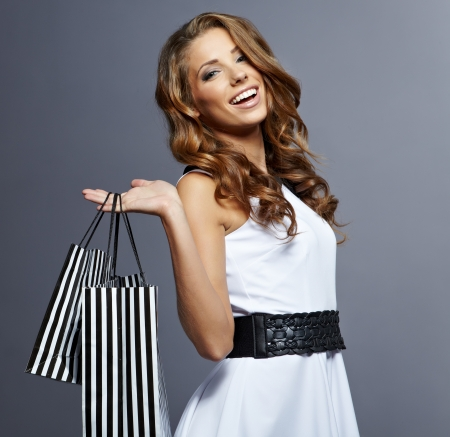 Shopping woman holding bags,  isolated on gray studio background   photo