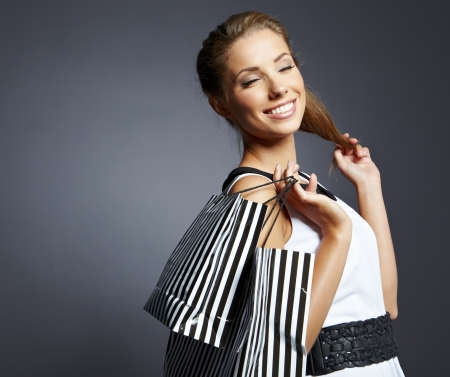 Shopping femme tenant des sacs, isolé sur fond de studio gris. Banque d'images - 15227213