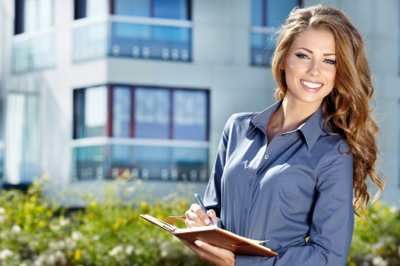 real estate business: Beautiful business woman on the background of the modern office