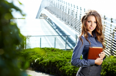 Realtor: Businesswoman standing outside a modern house  Stock Photo