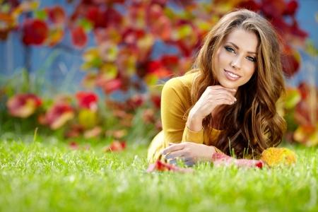 秋の公園で本で美しい少女