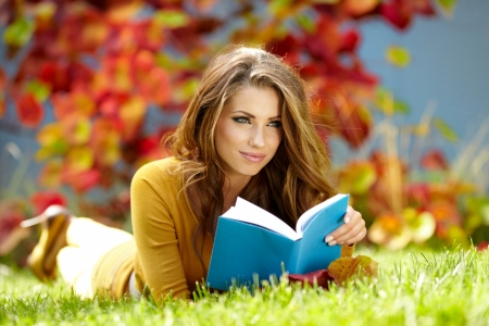 Jeune femme se trouve sur l'herbe verte et lit le livre contre autumn park Banque d'images - 15227238