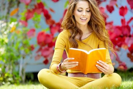 Jeune femme se trouve sur l'herbe verte et lit le livre contre autumn park Banque d'images - 15227249