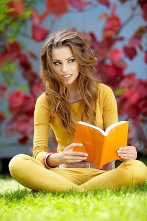 Young  woman lies on green grass and reads book against autumn  park   photo