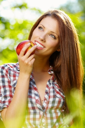 red hair beauty: Portrait of beautifu young woman with a basket of fruit at summer green park