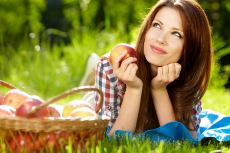 Portrait of beautifu young woman with a basket of fruit at summer green park  photo