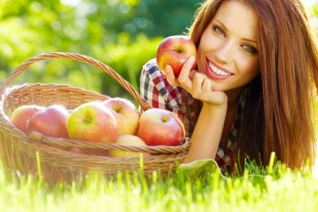 Belle femme dans le jardin avec des pommes