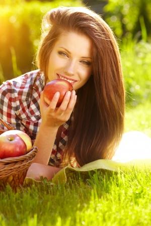 Retrato de mujer joven beautifu con una cesta de fruta en verano parque verde