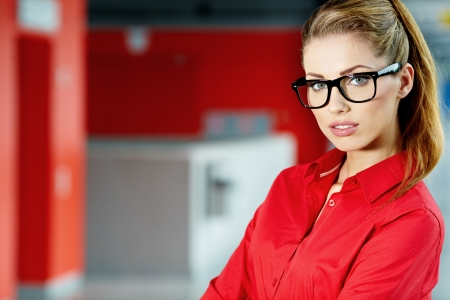 girl glasses: Young businesswoman against office windows