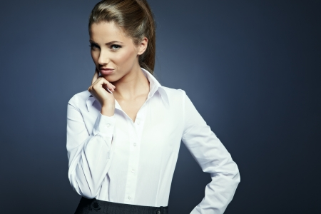 business woman standing: Portrait of a beautiful young business woman standing against grey background  Stock Photo