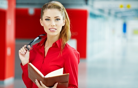 business woman standing: business woman holding glasses and looking at camera. Copy space  Stock Photo