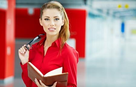 informe comercial: mujer de negocios la celebraci�n de las gafas y mirando a c�mara. Copiar el espacio