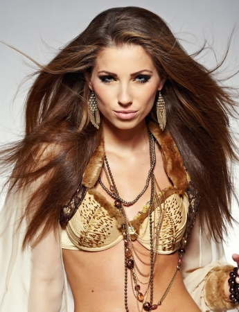 Sensual fashion woman with beautiful long brown hairs, posing isolated on grey photo