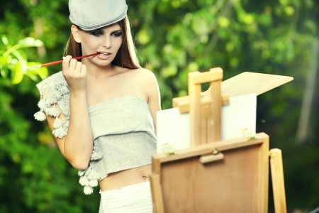 artist painting: Young woman painting landscape in the open air  Stock Photo