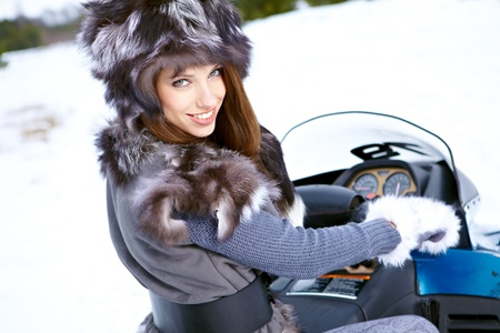 Smiling young woman riding a snowmobile Stock Photo - 15427869