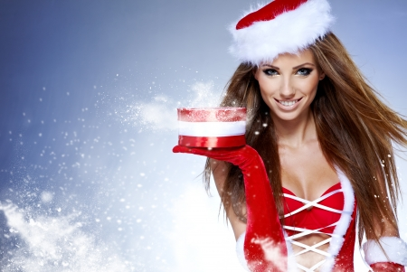 cute christmas: beautiful sexy girl wearing santa claus clothes with christmas gift