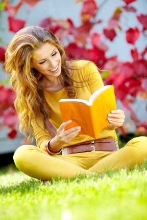 Portrait of a gorgeous brunette woman reading a book in the autumn park.  photo
