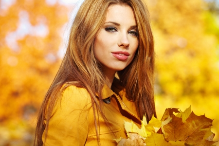 Portrait of beautiful young woman in autumn park.  photo