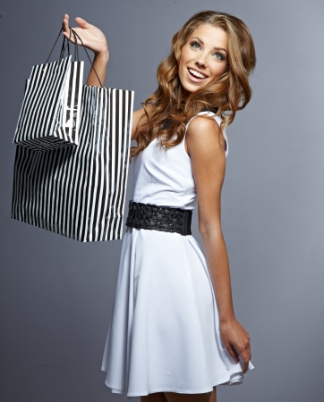 Woman holding shopping bags against a grey background  photo