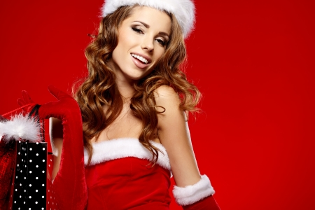 sexy santa woman holding colorful shopping bags  photo