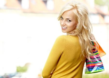 Beautiful woman in town holding shopping bags  photo
