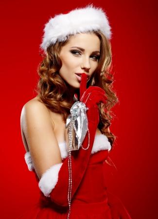 claus: Retrato de la hermosa chica sexy vistiendo ropa de Pap� Noel en fondo rojo