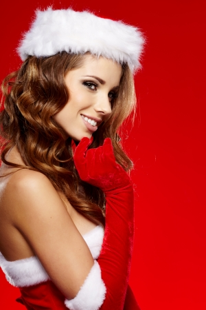 Portrait of beautiful sexy girl wearing santa claus clothes on red background  Stock Photo - 16038859