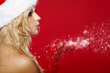 pretty young brunette woman dressed as Santa blowing on the snow on her hands Stock Photo - 16166123