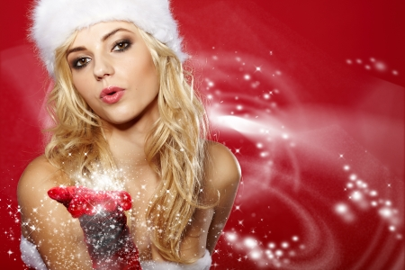 helpers: pretty young brunette woman dressed as Santa blowing on the snow on her hands  Stock Photo