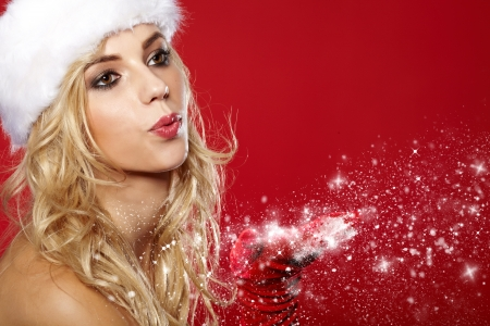 santa helper: pretty young brunette woman dressed as Santa blowing on the snow on her hands  Stock Photo