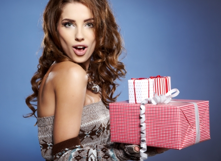 Girl opening x-mass present isolated on grey background  photo