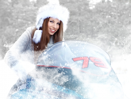 snowmobile: Smiling young woman riding a snowmobile