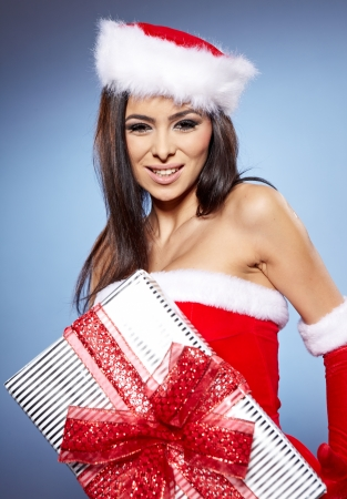 Christmas woman with gift, isolated on blue  background  photo