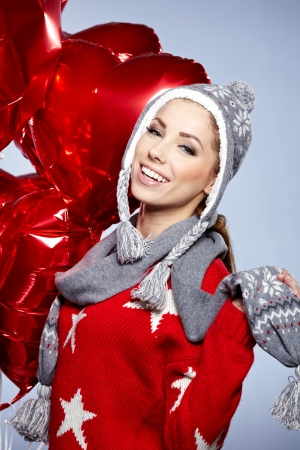 Cute young woman wearing warm winter clothing and holdingred  heart posing in studio Stock Photo - 17159577